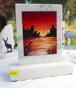 Sunset over water with silhouette trees painted on marble
