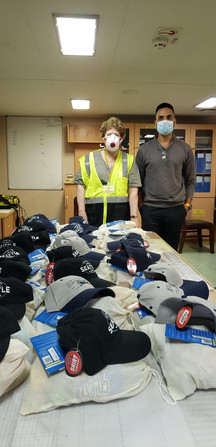 Barbara and Captain admire the display of hats the Capt.  bought for crew gifts and goodies provided by ITF grant.