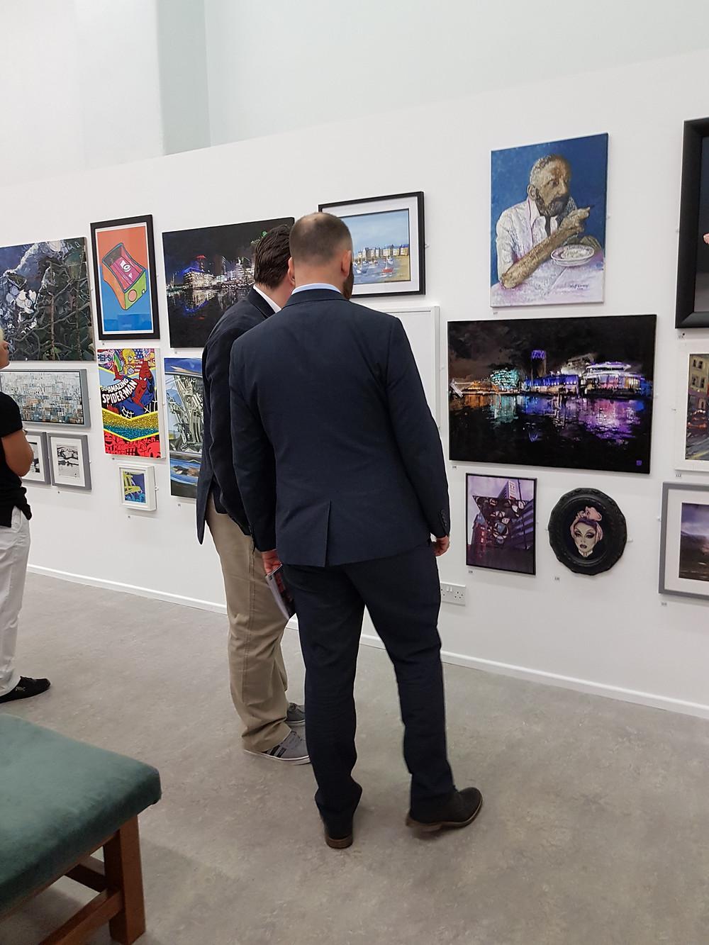 Two people viewing Ben Ark Artwork