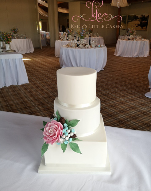Three tier white wedding cake with square base.