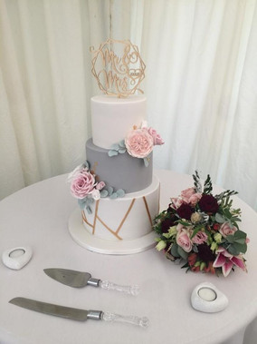 Grey and white wedding cake with gold geometric design,handmade sugar flowers and leaves.