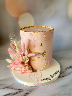 gold leaf and pink cake with dried flowe