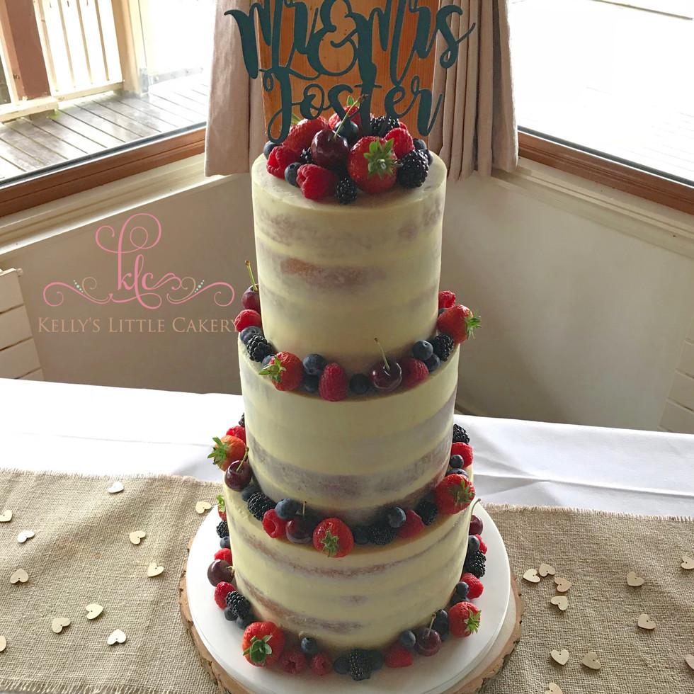 Semi naked rustic wedding cake with fresh fruit