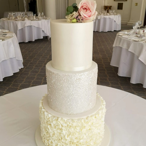 All white three tier cake, with ruffles, sparkles and pearlescent