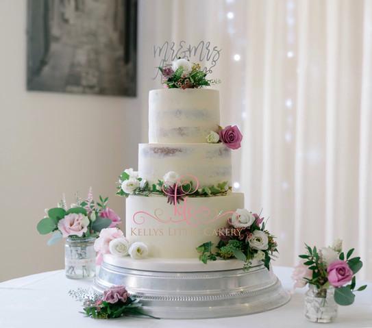 Semi naked rustic wedding cake with fresh flowers