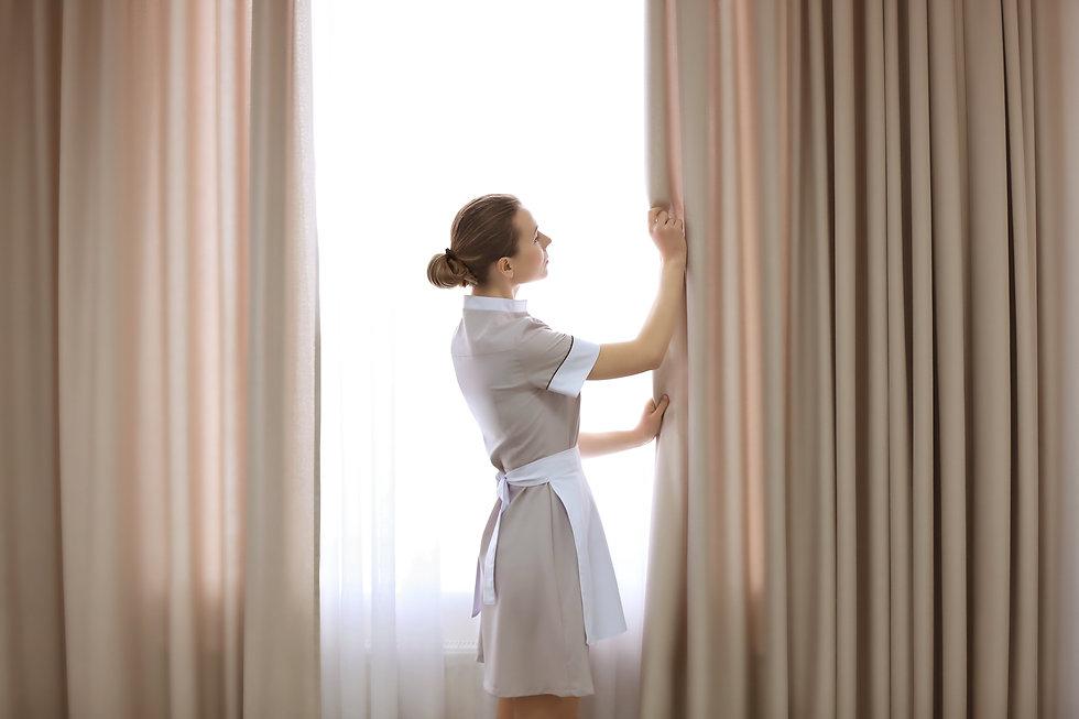 Hotel service concept. Chambermaid adjus