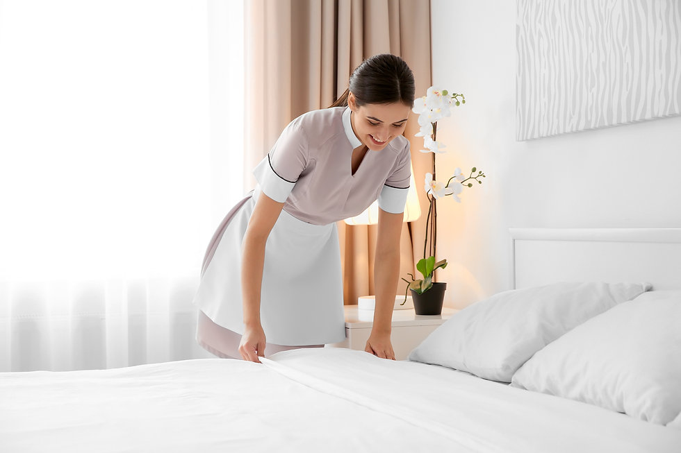 Young maid making bed in light hotel roo