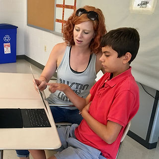 Lisa Mihalich Quinn holding a letterboard while working with a student during Reach Every Voice Summer Institute
