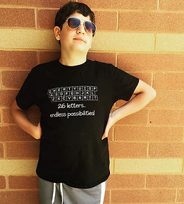 "Student attends REV Institute. Wearing sunglasses and a shirt that reads ""26 letters...endless possibilities!"""