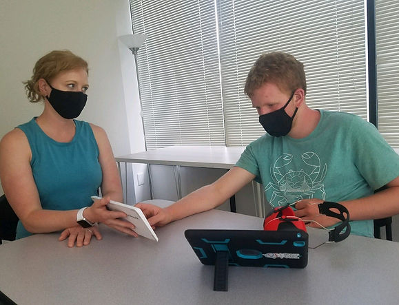 A student is typing on a keyboard held by a teacher. Both are wearing masks. His ipad sits on the table.