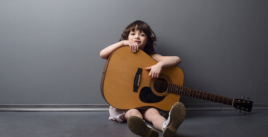 donate guitars to kids in need . Child with guitar