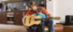 young child plying guitar in assisted lesson | Guitar lesson is in St Albans