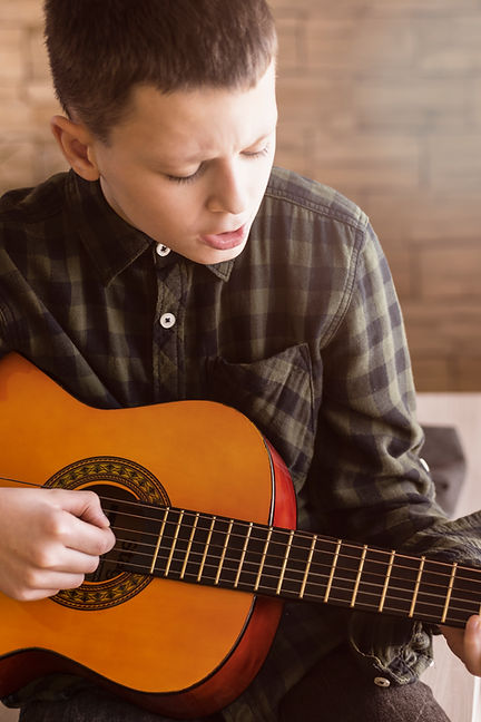 Young boy playing classic acoustic guitar in Guitar Lessons St Albans