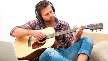 adult practiing guitar after St alabans guitar lesson