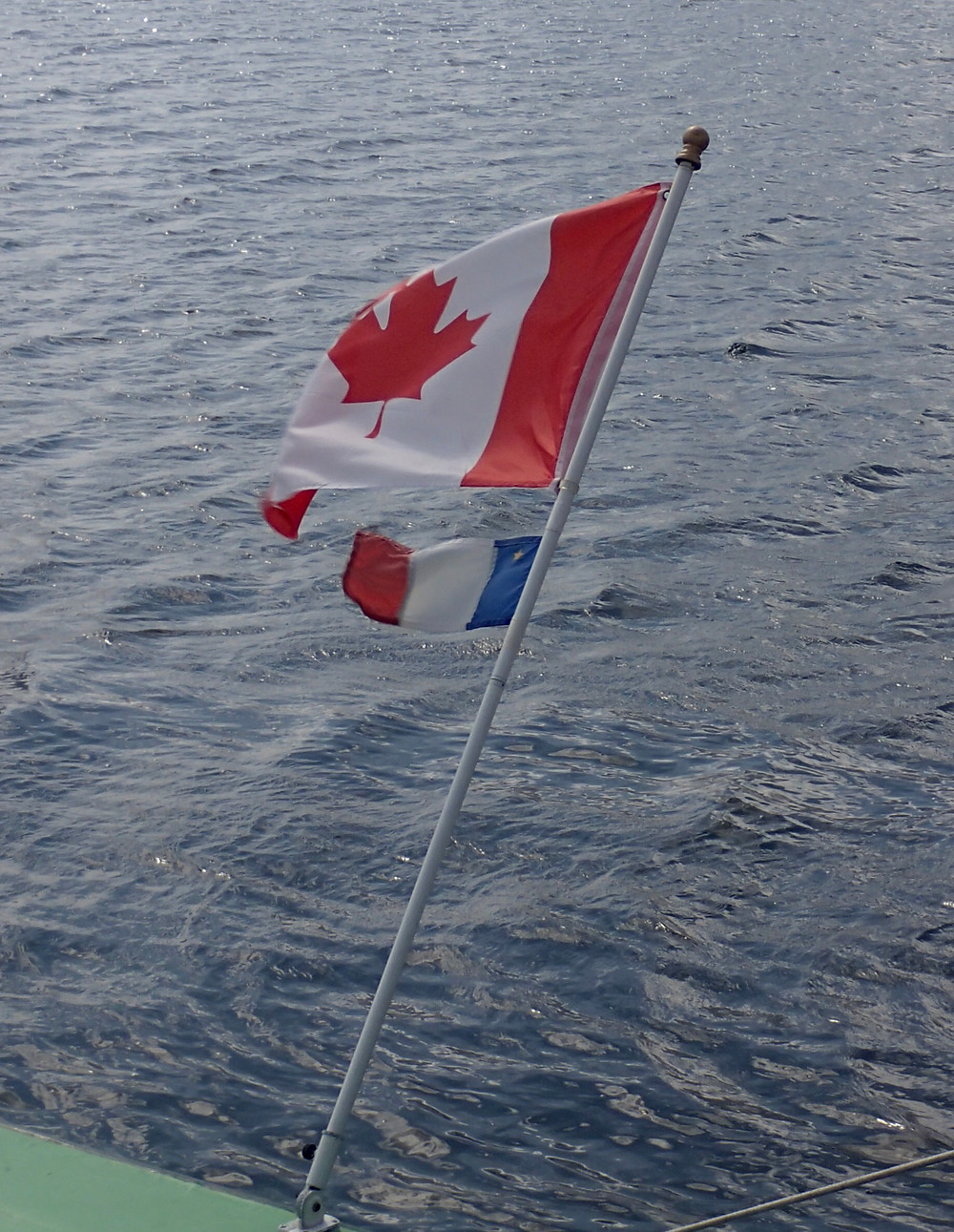 Acadian and Canadian flags on a boat