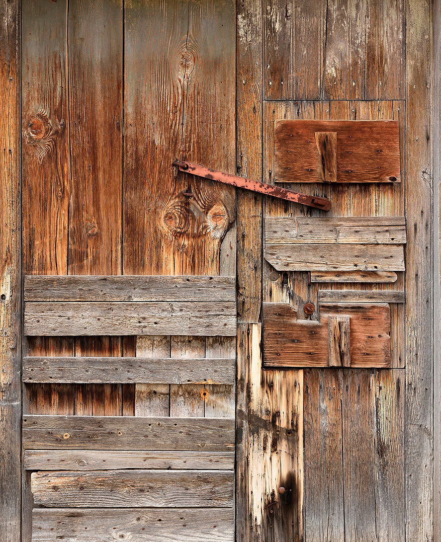 Rustic wood door of browns and textured detail, Matera, Italy