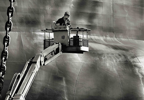 Man in a crane in front of a commercial tanker in a shipyard