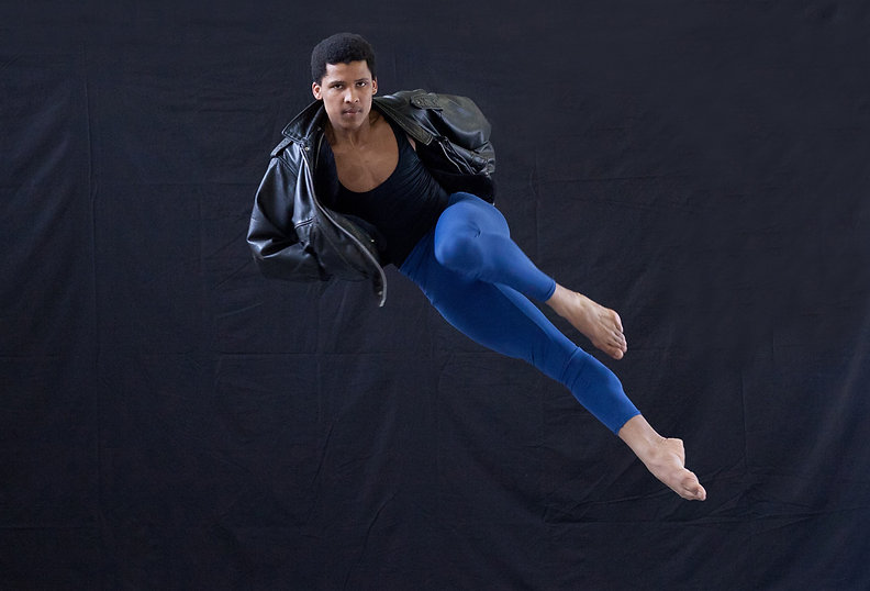 Single male ballet dancer in mid air