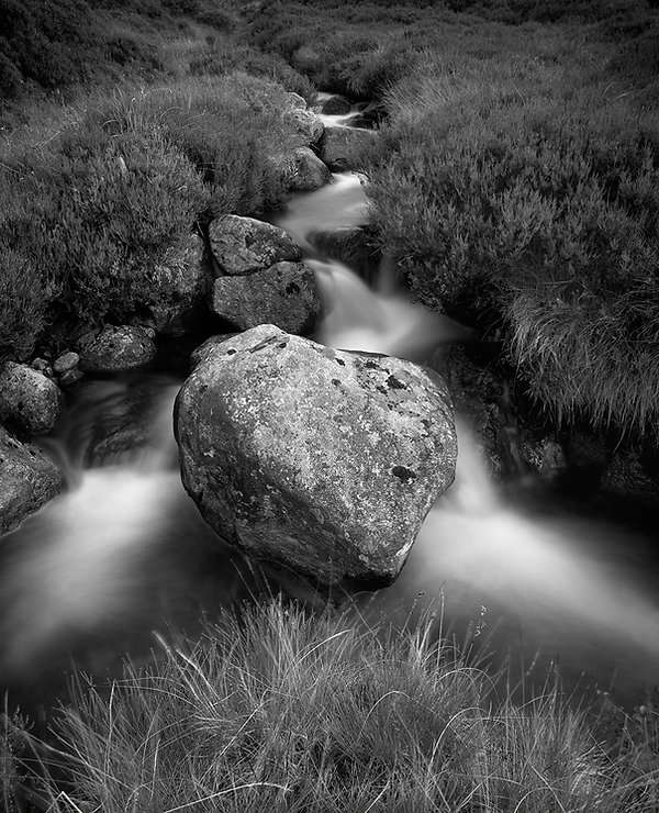 A boulder in a Scottish stream with water flowing around it