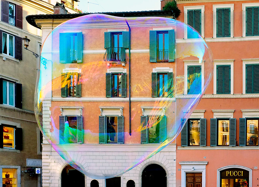 An extra large soap bubble with a building behind it, Rome