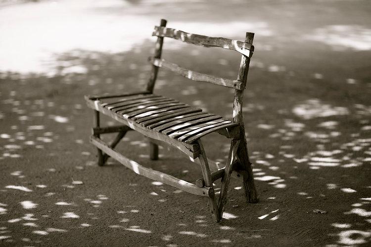 A rough wooden bench in dappled light ion Moruku botanical gardens, Madike, S Africak