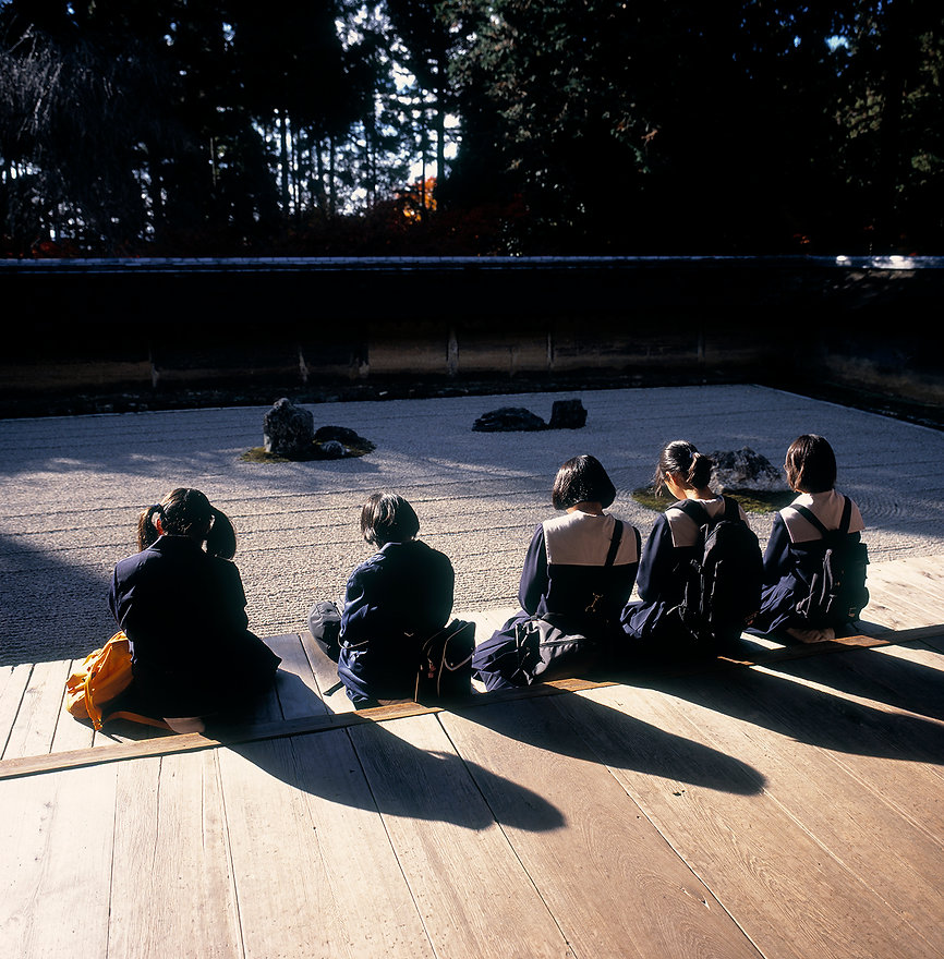 School girls meditate in front of the famous gravel field in the Ryoan-ji temple, Kyoto, Japan
