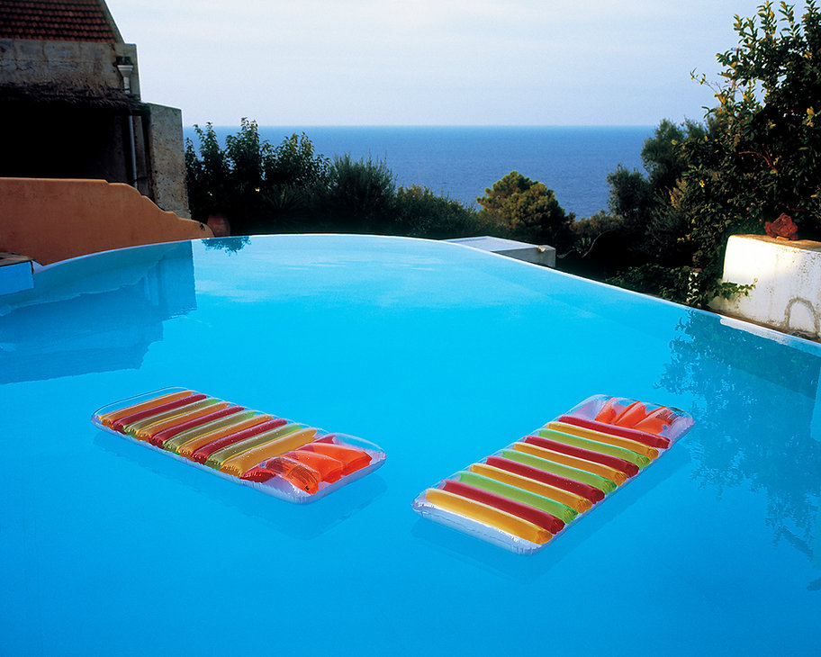 Two multi-coloured lilos on a pool in Salina, Italy