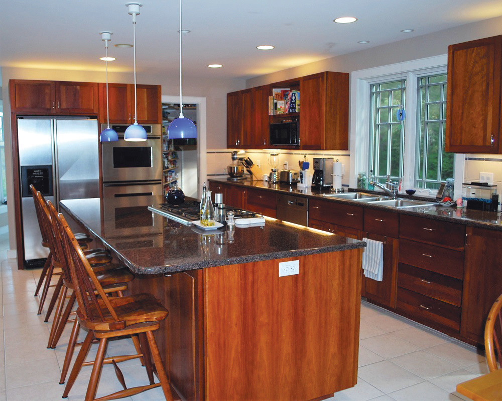 Beautiful open concept kitchen with large, granite island, stainless steel appliances and dark wood cabinets