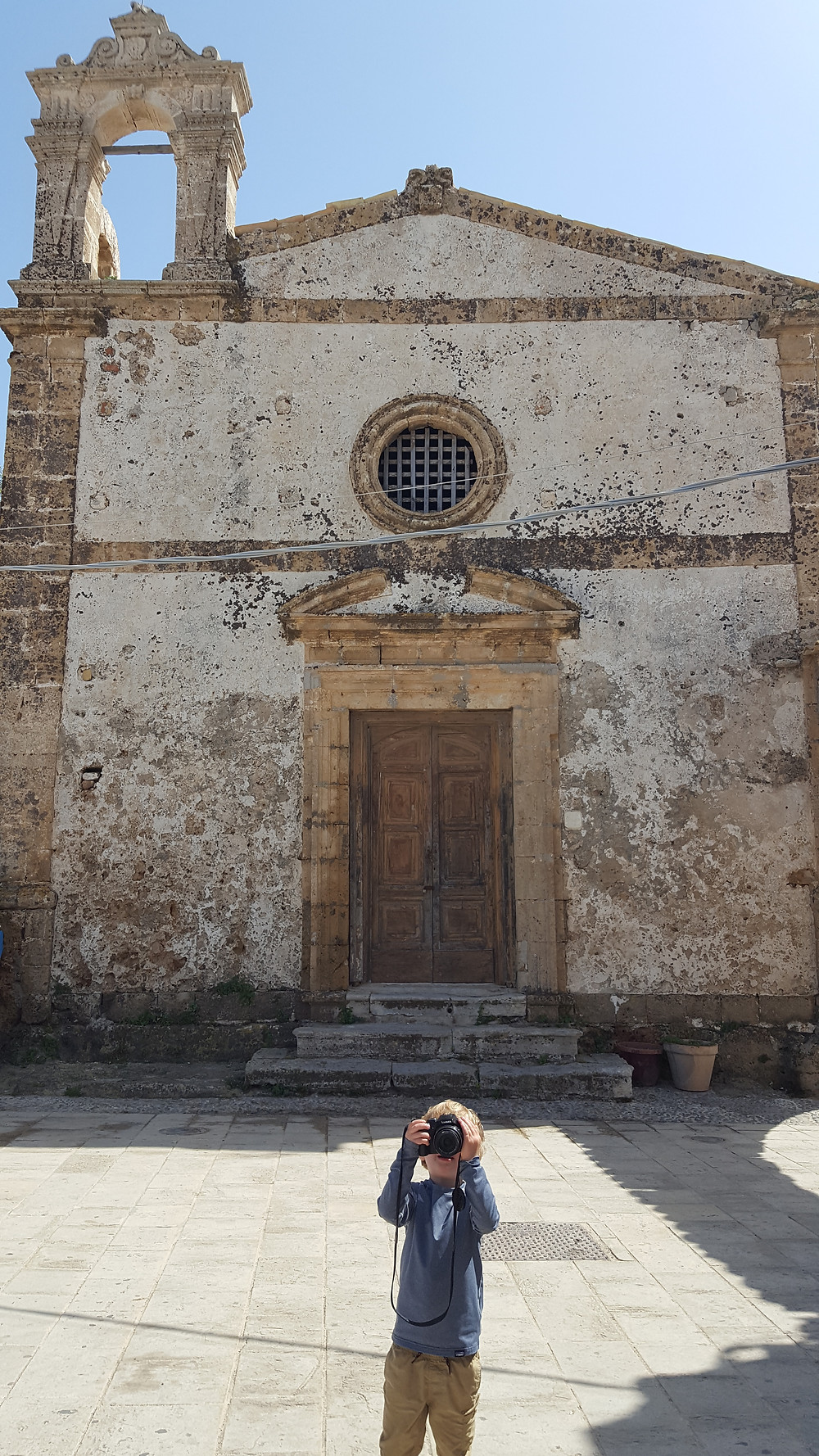 Boy taking a picture in front of a church in Sicily Italy