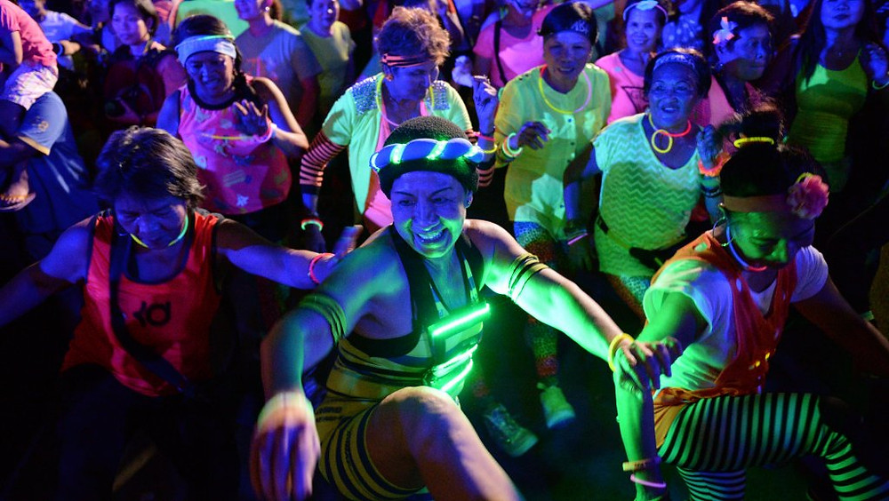 Women wearing glow in the dark costumes dancing