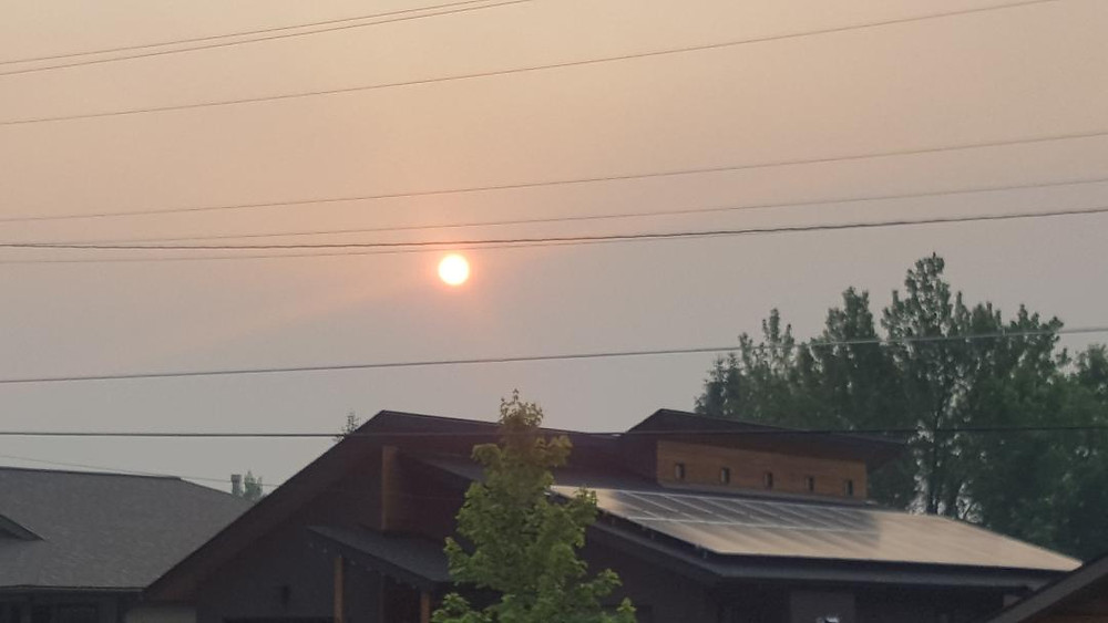 Smokey sun behind a house with solar panels