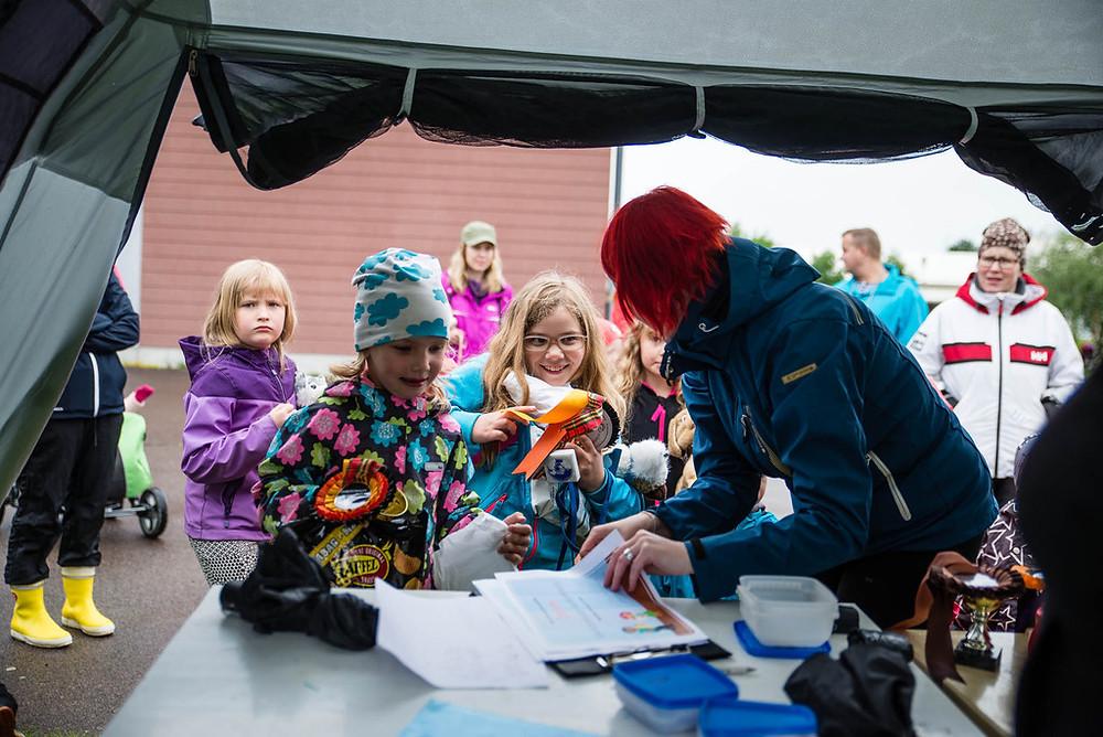 Lapsi ja lelukoira - kisan osallistujat noutamassa palkintojaan