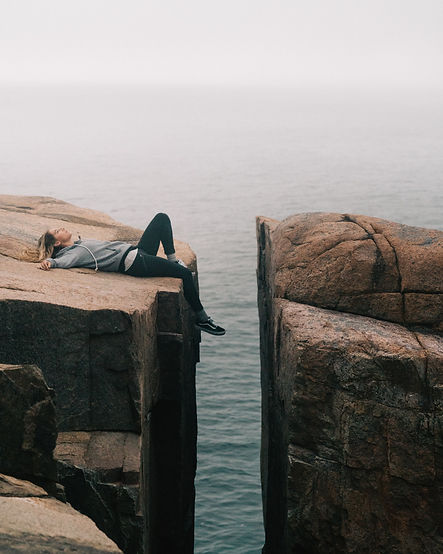 Exhausted, sad person lying down on a cliff.
