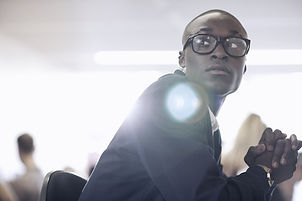 Young black professional looks anxiously over his shoulder.