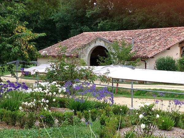 l'entrée du Chai de Montaulieu vu par dessus des fleurs