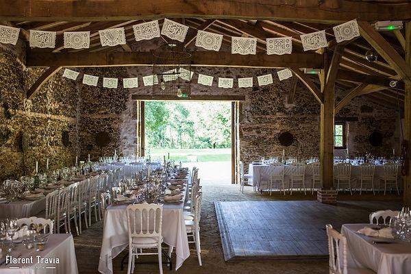 Tables pour un mariage avec chaises blanches anciennes et fanions