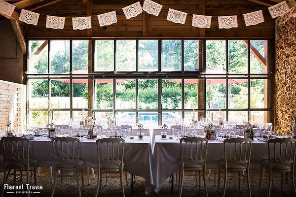 Tables de mariage avec chaises anciennes blanches devant la grande verrière du Chai de Montaulieu
