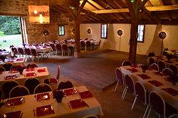 Grandes tables avec chaises rouges pour un diner dans le Chai