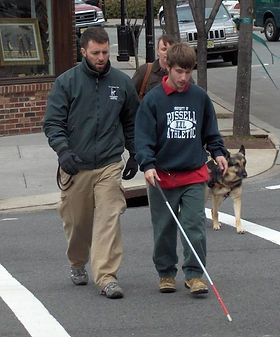 Student with a long cane crossing a street with dog guide and handler in the background.