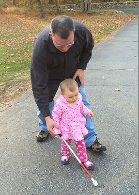 Toddler receiving cane instruction from COMS John Kelly.