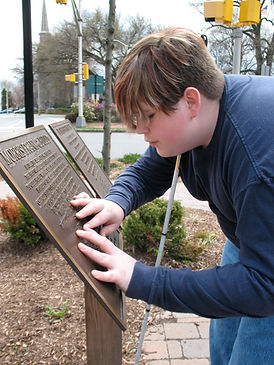 Teenager reads a Braille sign.
