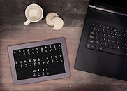 Image of the Braille alphabet on a slate next to an open laptop computer.