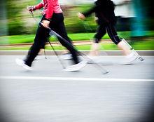 Woman nordic walking race on city street
