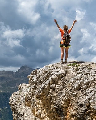 Person on top of a mountain, arms raised