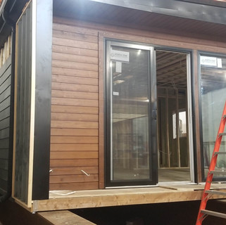 Fiber cement board and engineered wood siding is installed to the exterior.
