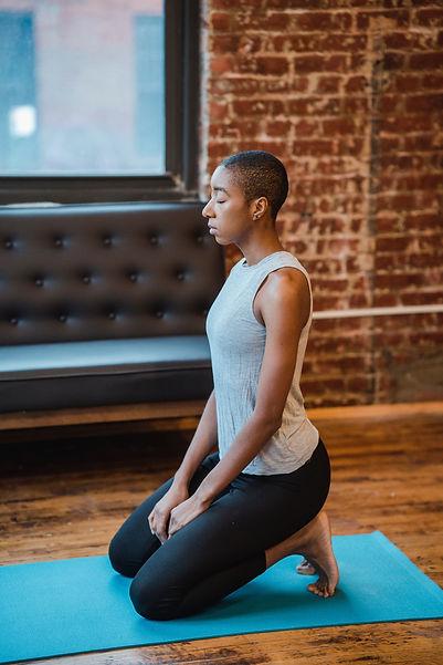 woman of color on yoga mat.jpg