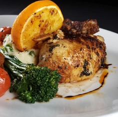 Rotisserie Chicken with whipped red new potatoes, broccolini, topped with an orange wedge and tamarind sauce