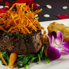 Peppercorn-Crusted Filet over sauteed spinach and served with duo au gratin potatoes, in au jus truffle olive oil