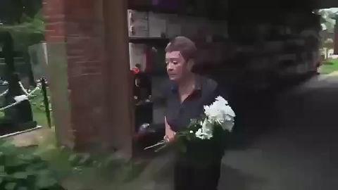 Ольга Александровна возлагает цветы на могилу своего мужа, Гелия Трофимовича Рябова