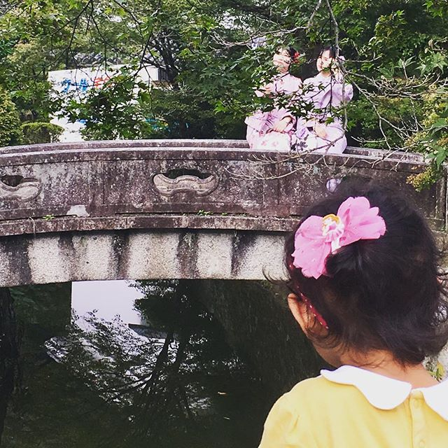 Pretty ladies in kimonos posing on majestic bridge being admired by a little girl and photographed b